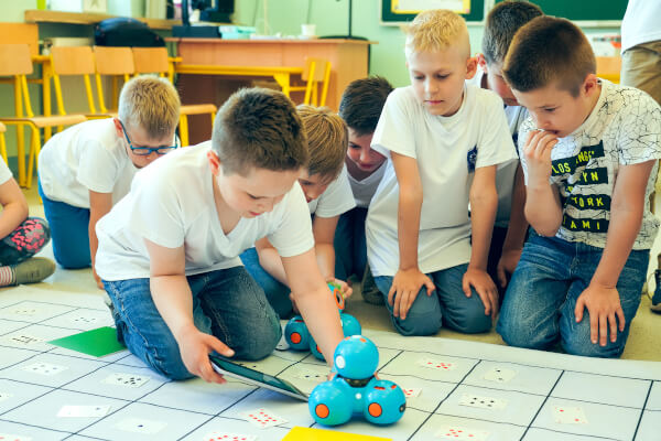The picture shows 8 children who are playing with a toy robot on a toy mat.