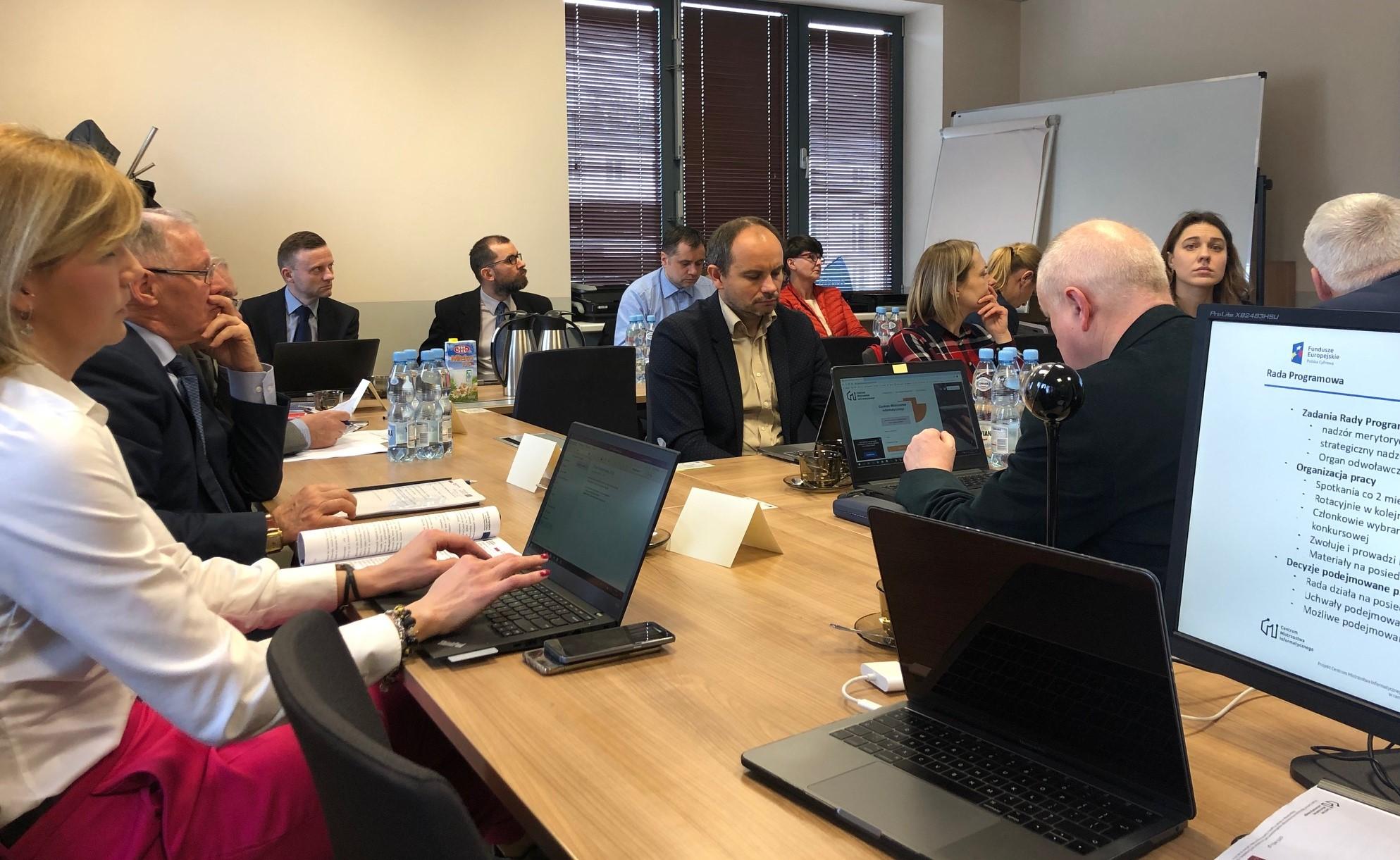Osoby odpowiedzialne za projekt CMI siedzą przy stole podczas spotkania Rady Programowej.