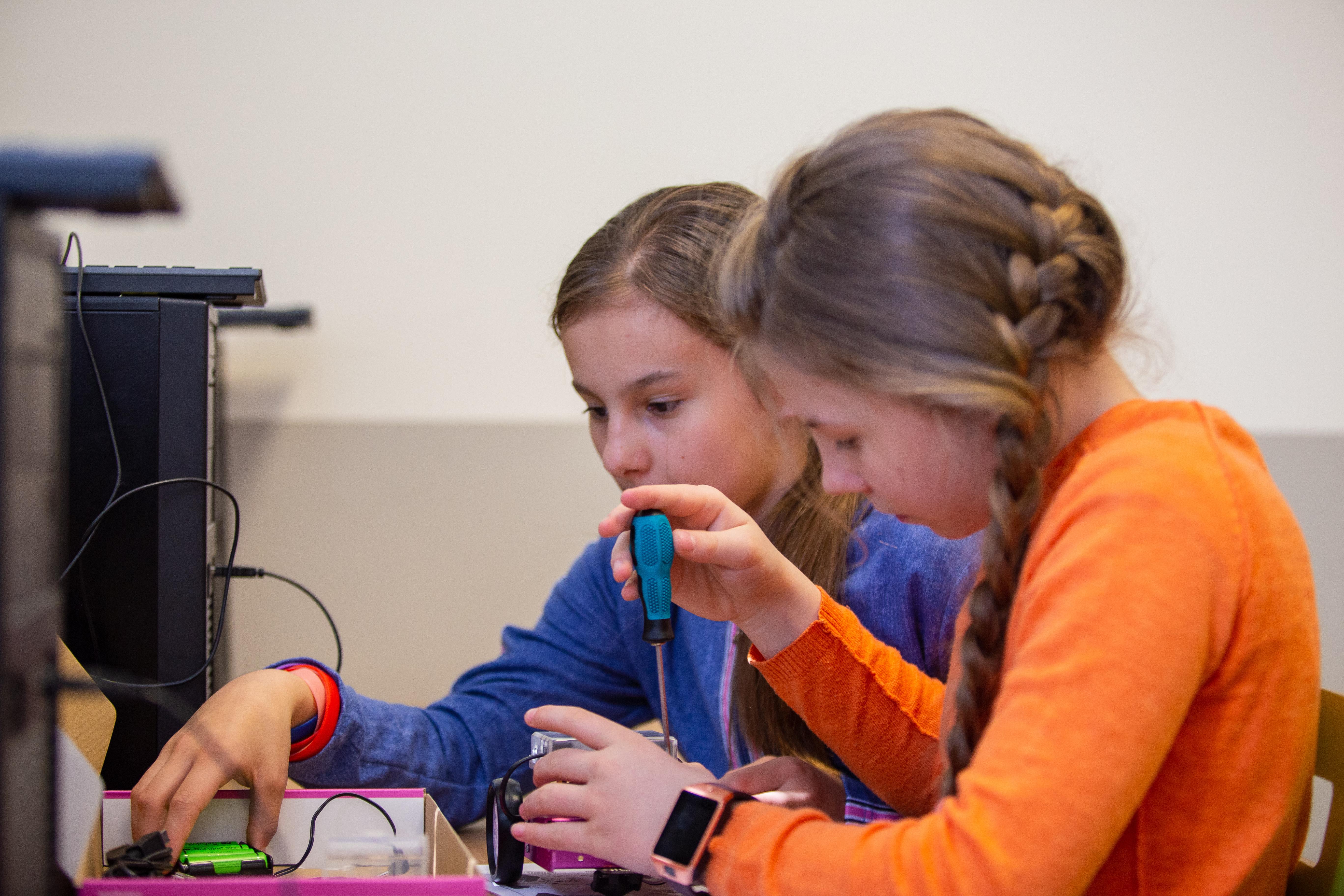 Dziewczyny naprawiają mały robocik śrubokrętem.
