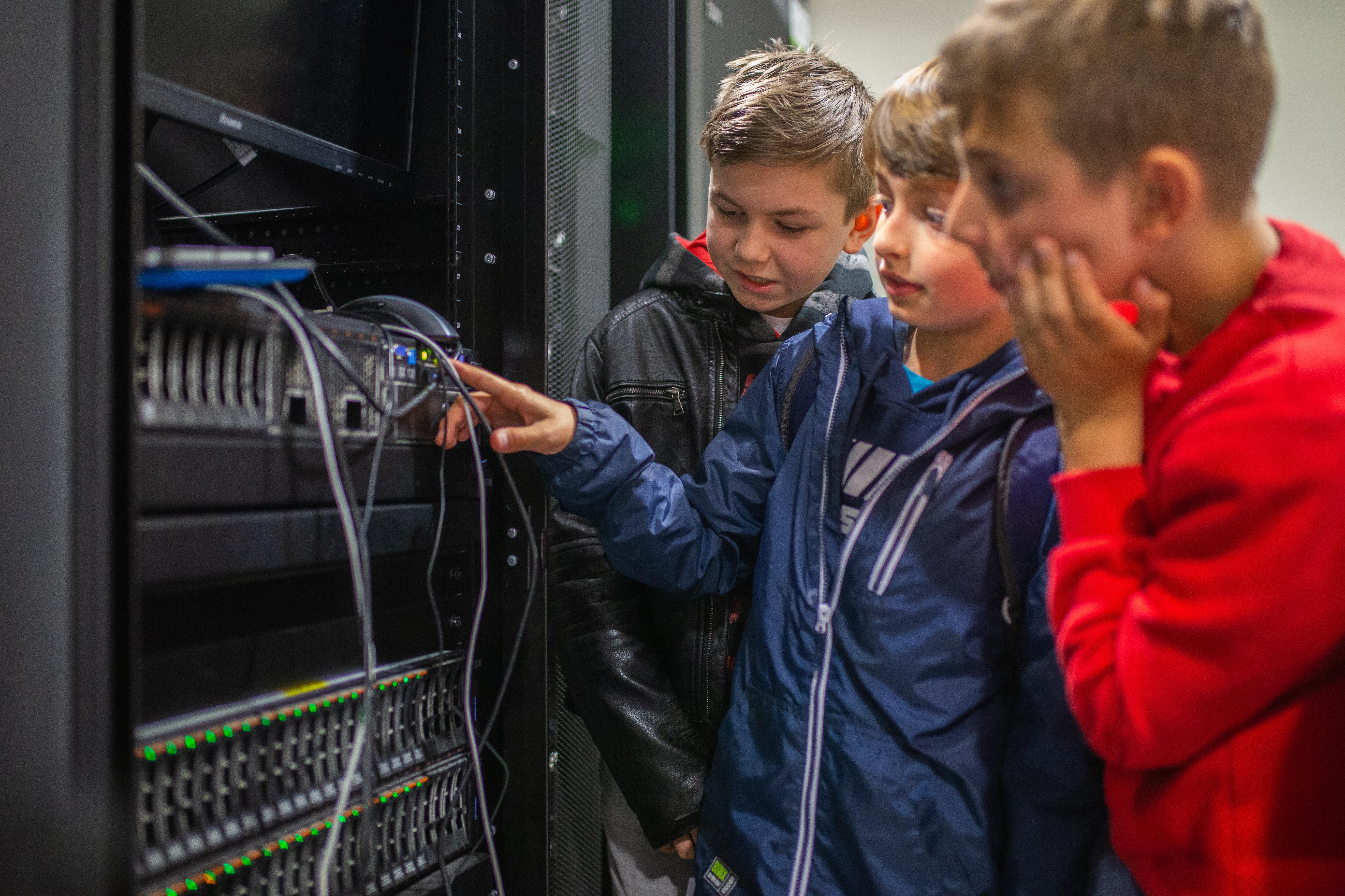 Trzech chłopaków przy skrzynce serwerowej.